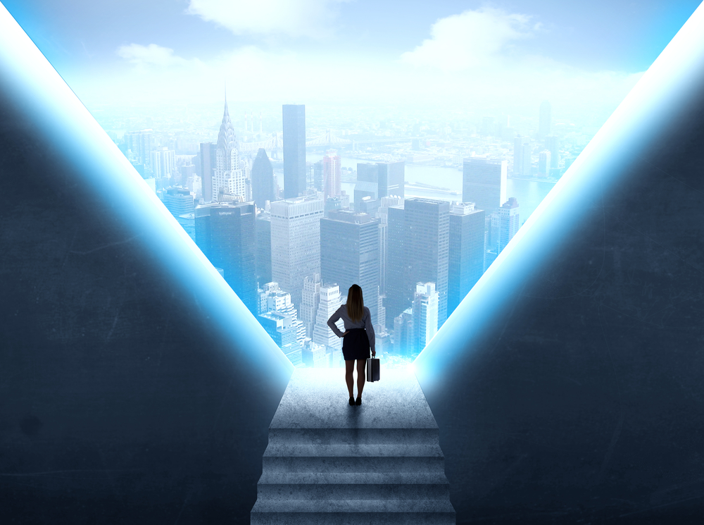 Businesswoman standing in the prison and looking at the cityscape
